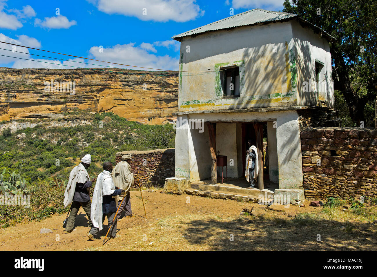 Pilgrims at the gate to the orthodox rock-hewn church Medhane Alem Kesho, Tigray region, Ethiopia - Stock Image