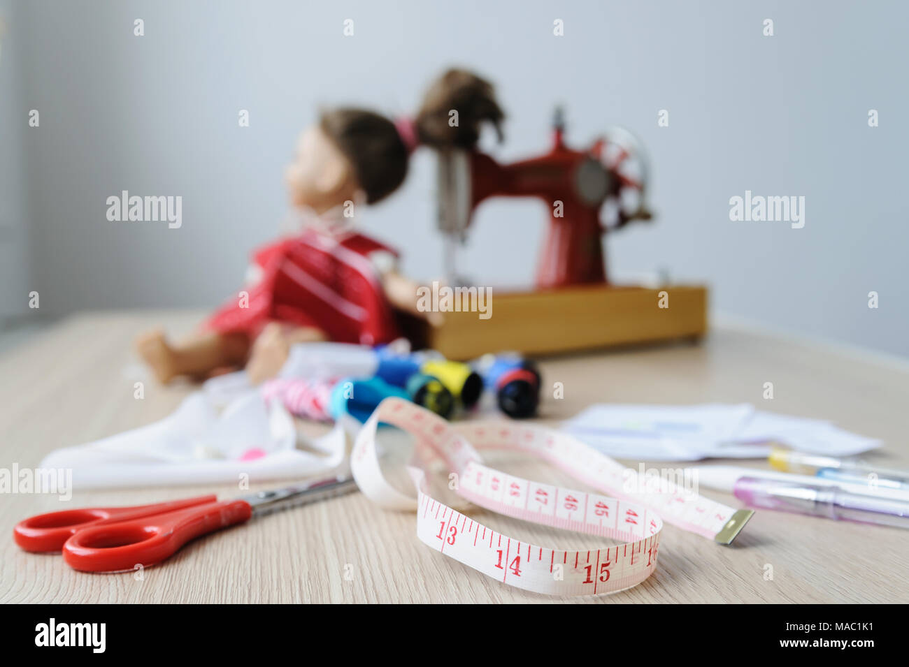 Workplace of seamstresses. On the desktop there is a measuring tape, scissors, pens, pencils, spools, fabric, a sewing machine and a doll. - Stock Image