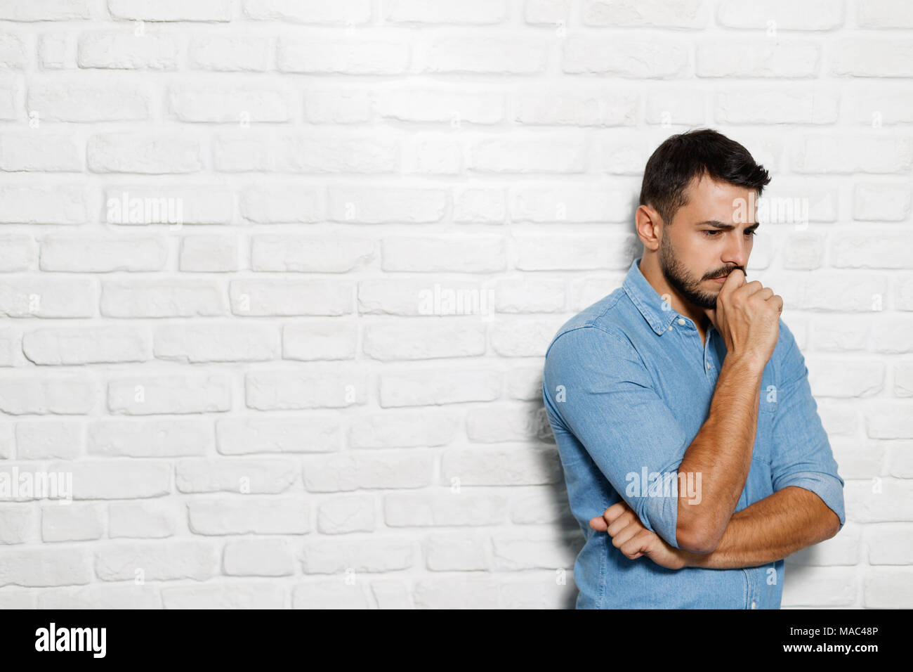 Portrait of puzzled man having doubts. Doubtful Italian business man thinking. Copy space - Stock Image
