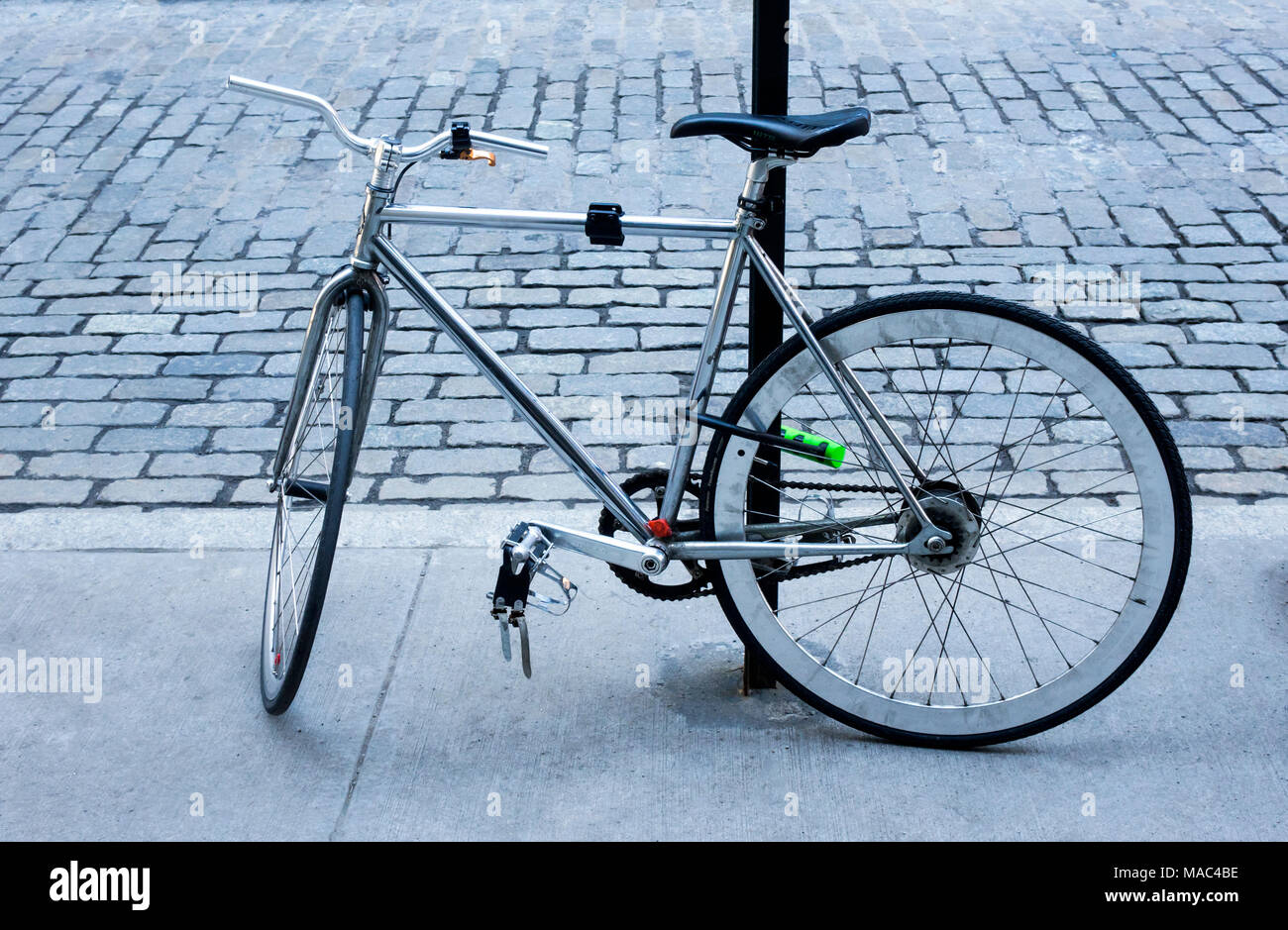 Man's bicycle secured to a post on a cobblestone street in New York City - Stock Image