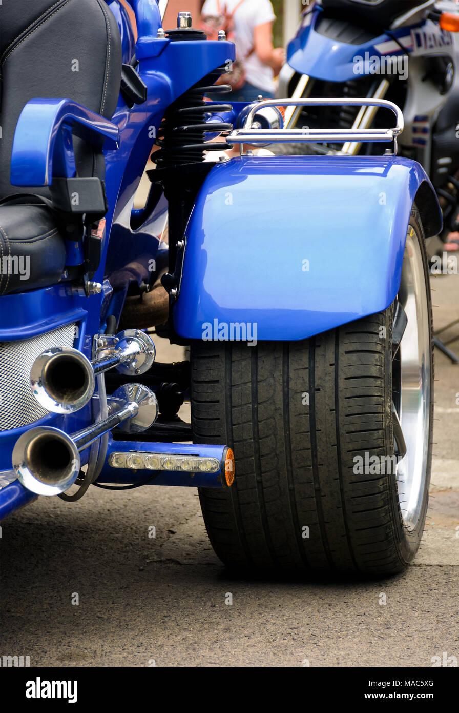 rear side of a blue motorcycle. lovely detail shot of lights and shiny exhaust pipes - Stock Image