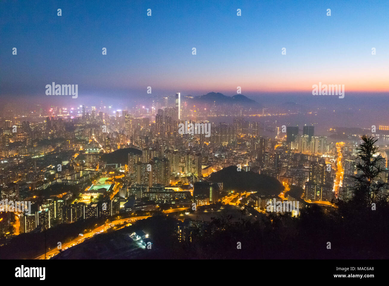 Sunset view of high rises by Victoria Bay dominated by International Financial Center, Hong Kong, China - Stock Image