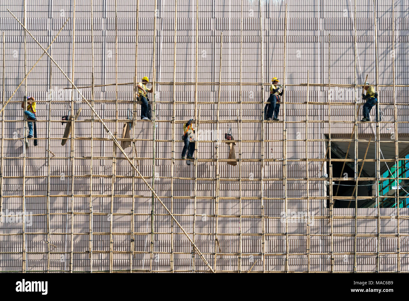 Construction workers on scaffolding outside a new construction, Hong Kong, China Stock Photo