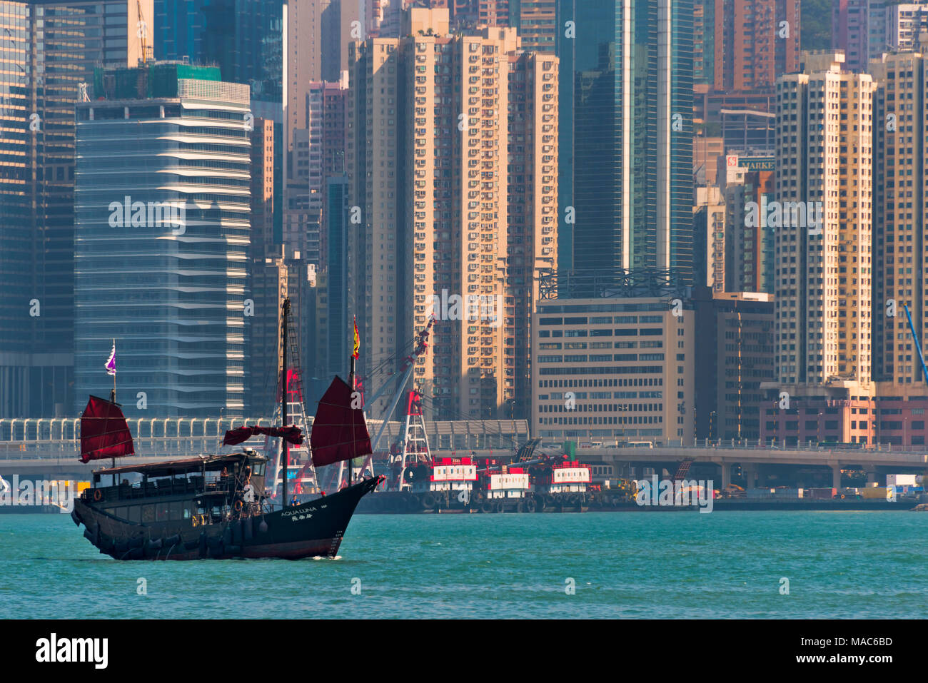 Junk boat and high rises in Victoria Bay, Hong Kong, China - Stock Image