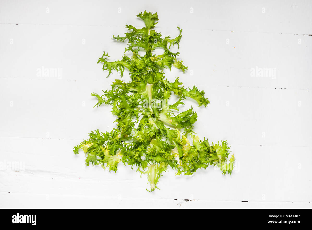 Christmas Food background. Christmas tree made from fresh frise on white background. Healthy holiday food, vegan, vegetarian and diet concept. Stock Photo