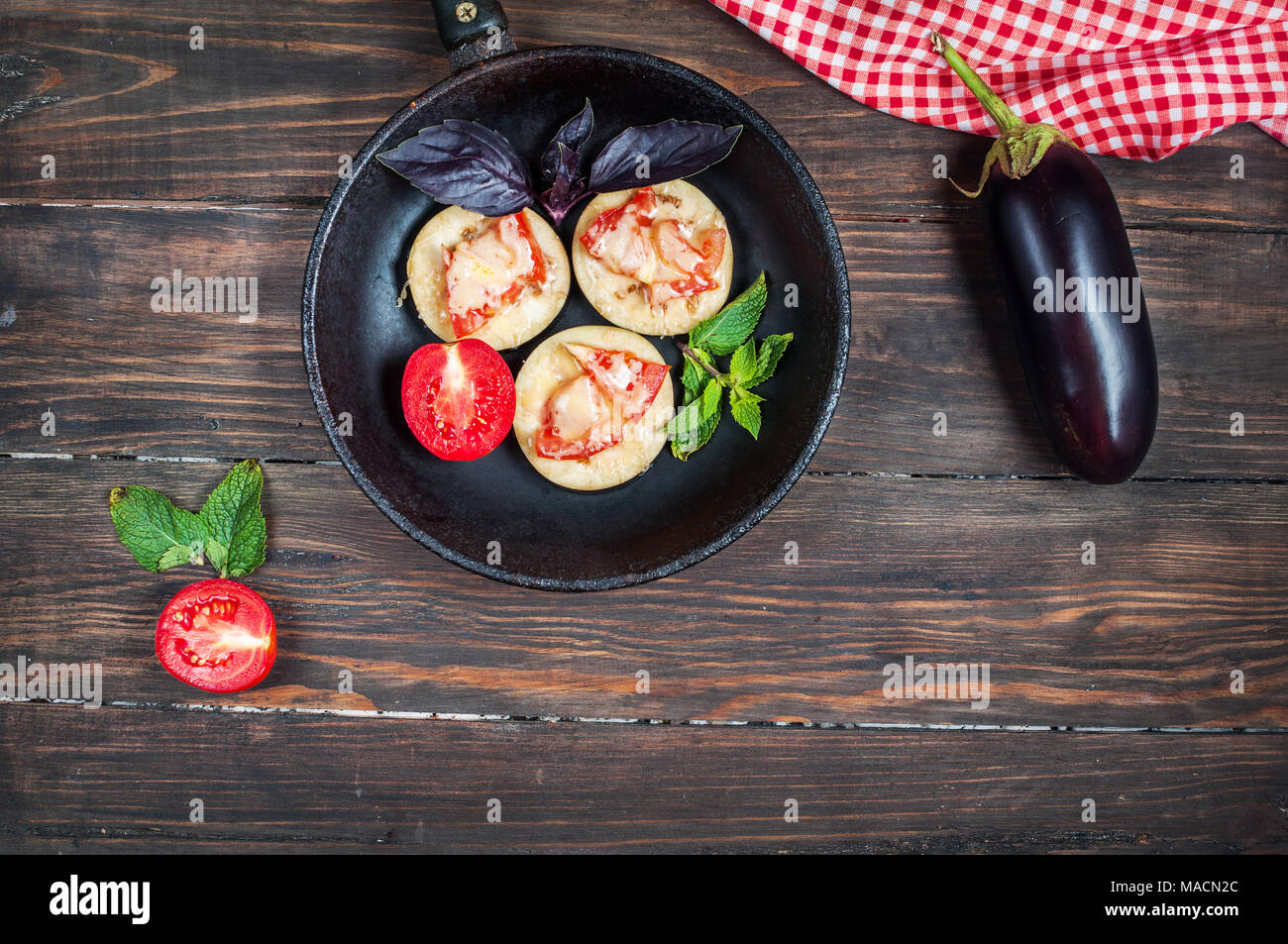 Healthy eggplant with cheese, tomatoes and basil on a pan against rustic wood. Stock Photo