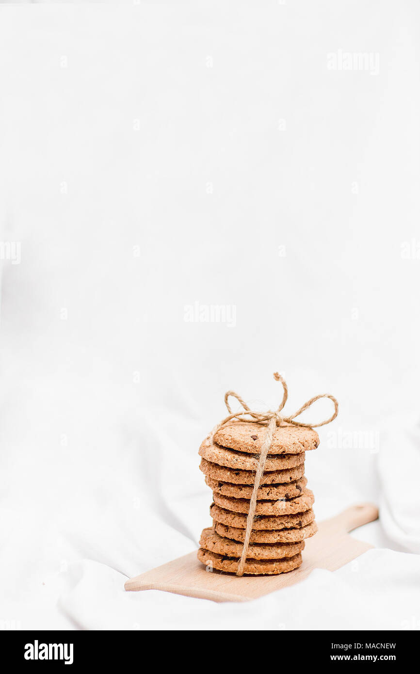 Sweet homemade cookies on a wooden board and white background - Stock Image