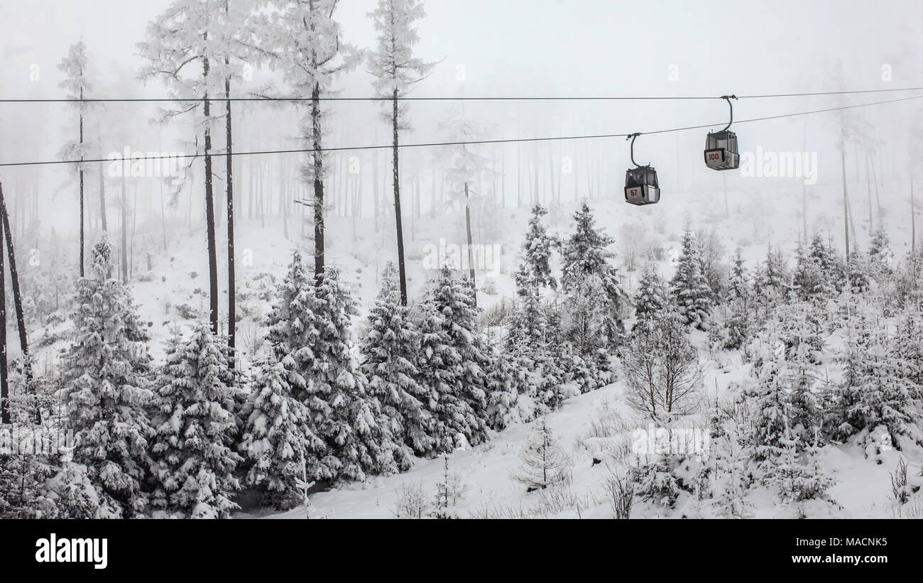 Two chairlift cabins passing each other on gray winter overcast day. Tatranska Lomnica ski resort, Slovakia - Stock Image