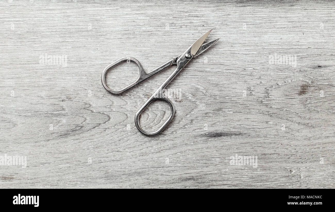 Manicure cuticle scissors on laminate flooring that looks like white wood table. - Stock Image