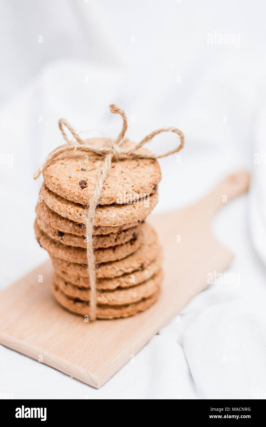 Sweet homemade cookies wrapped with rope on a wooden board and white background - Stock Image