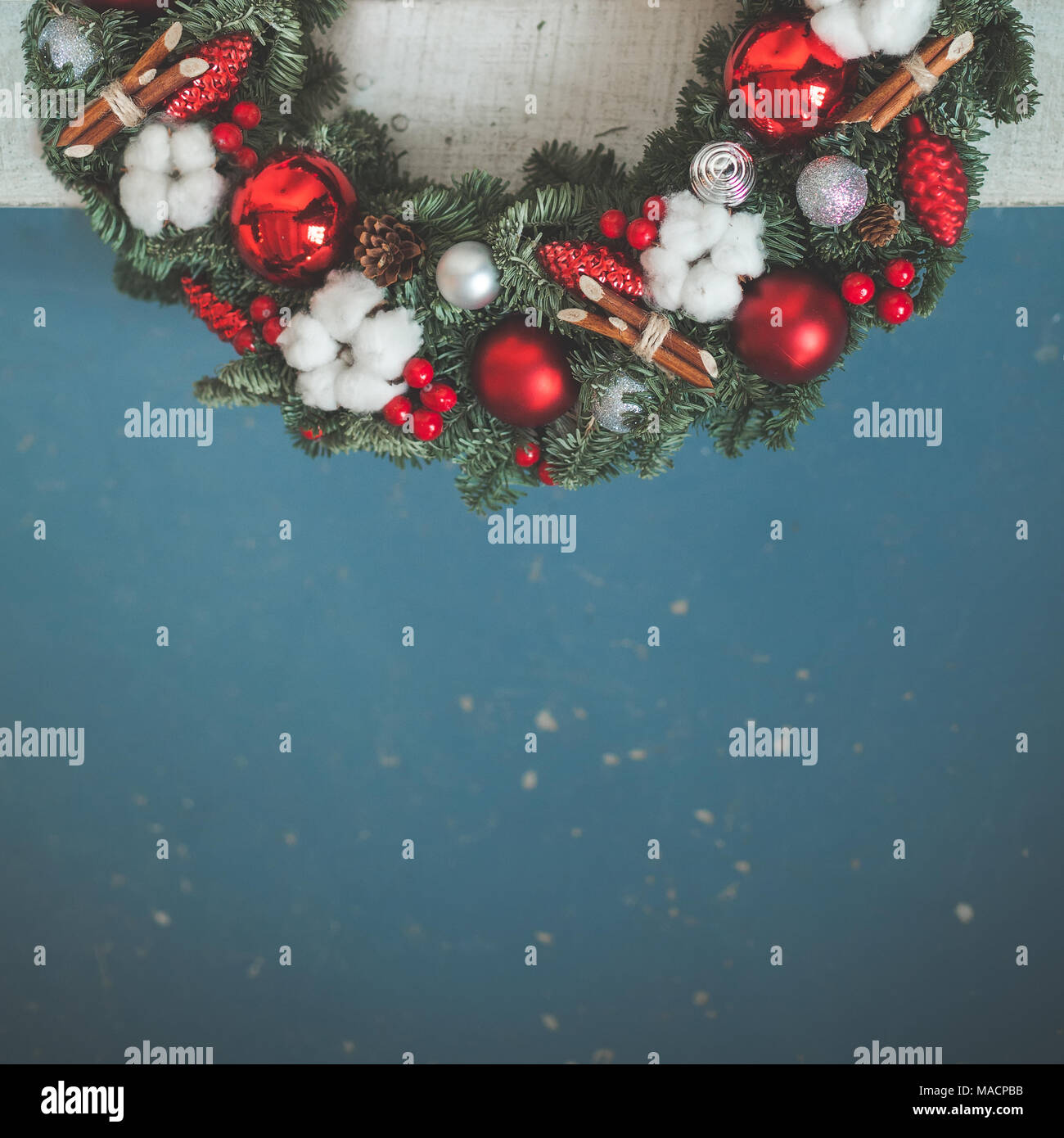 Christmas Background with Green Xmas Tree Twig, Red Glass Balls and New Year Decorations on Blue Background - Stock Image