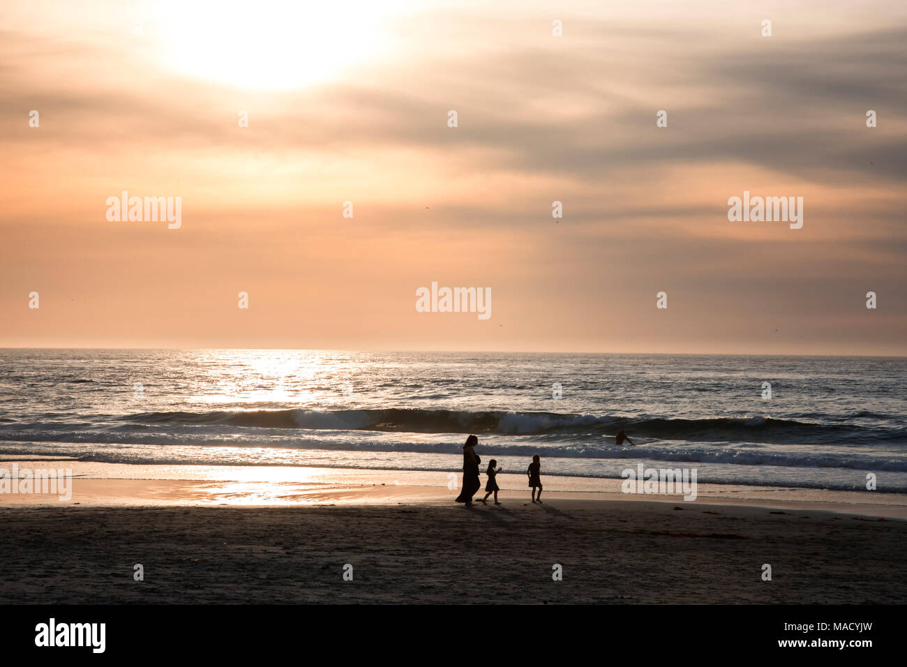 Family Walking on Asilomar Beach in Pacific Grove, California at Sunset Stock Photo