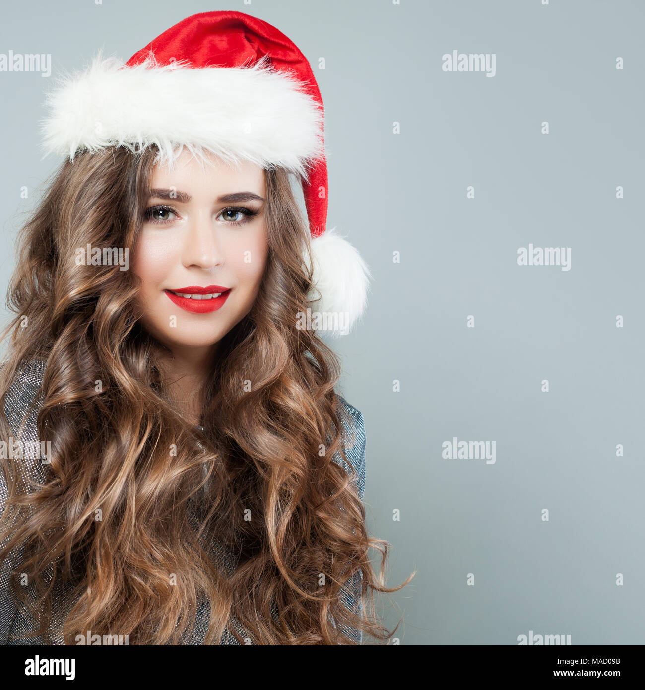 9d40a6393bad4 Christmas Woman Fashion Model wearing Santa Hat on Background with Copy  space. Cute Young Woman Fashion Model with Curly Hair and Red Lips Makeup  Smil