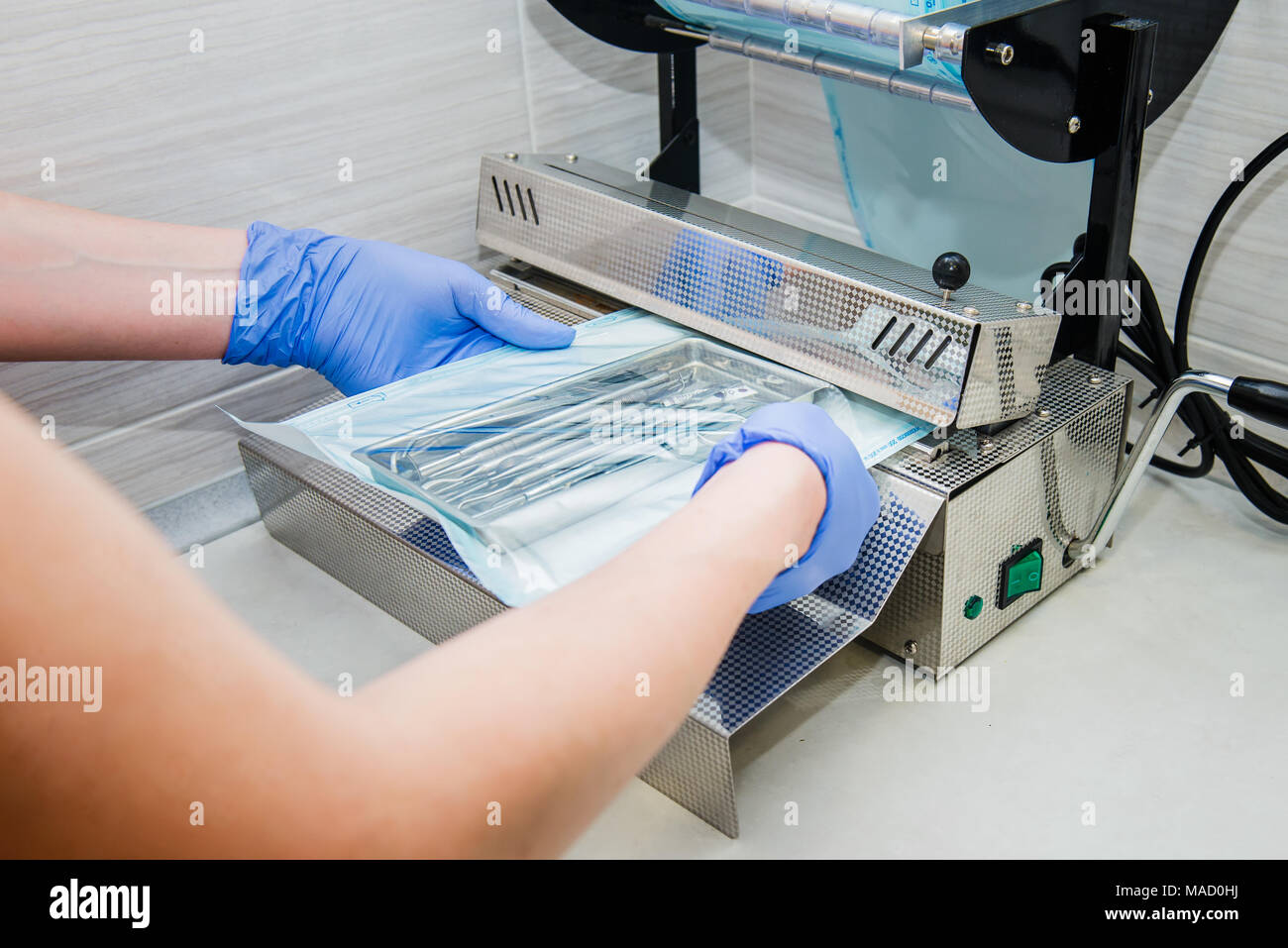 Close up dentist's assistant hands in gloves packing dental instrument set for autoclaving in a plastic bag using vacuum packing machine. Sterility and safety care concept. Selective focus. - Stock Image