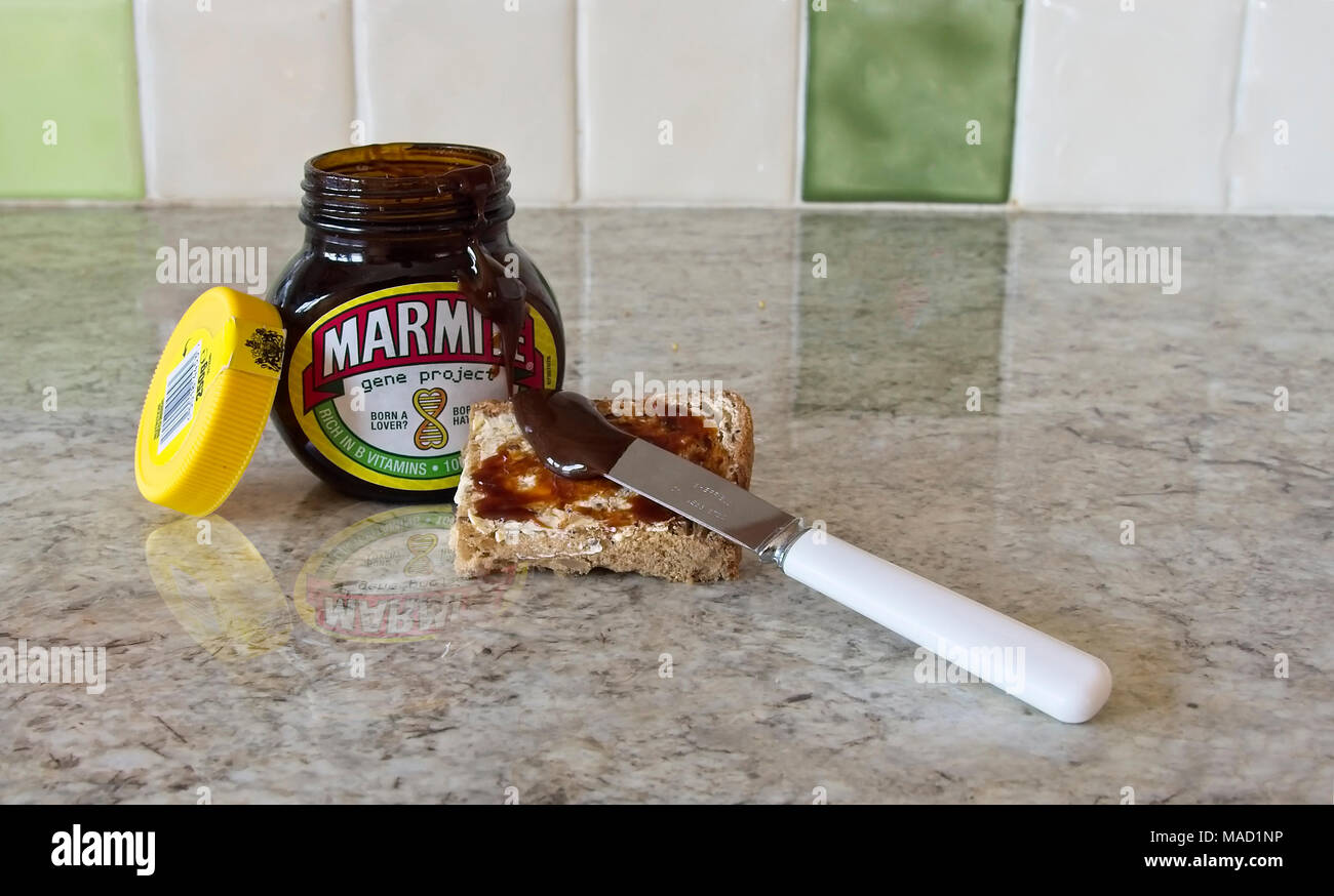 Opened jar of marmite with spread on piece of bread. - Stock Image