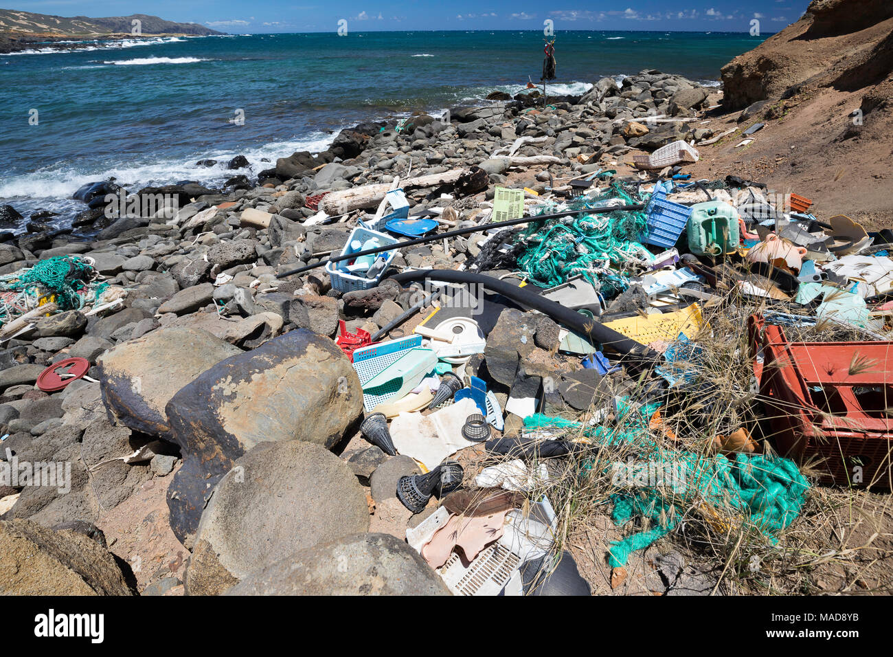 Much of the north side of the island of Molokai in inaccessible. Trade winds blow onshore regularly bringing with them piles of plastic that has been  - Stock Image