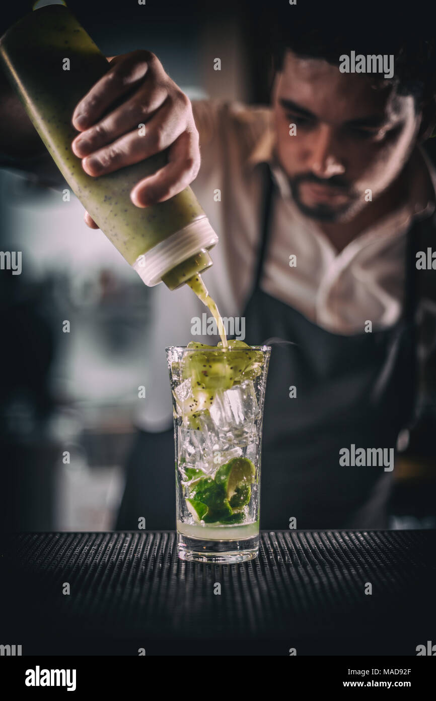Barman pouring sweet syrup into the fresh sour lime and kiwi cocktail on the bar counter - Stock Image