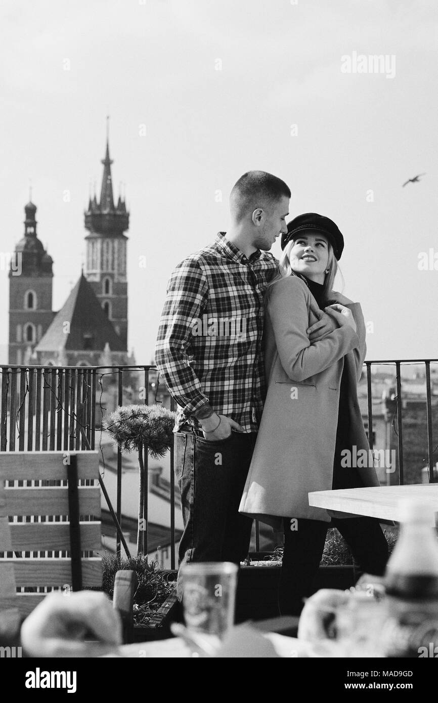 Lovely couple stand on city landscape and hug each other - Stock Image