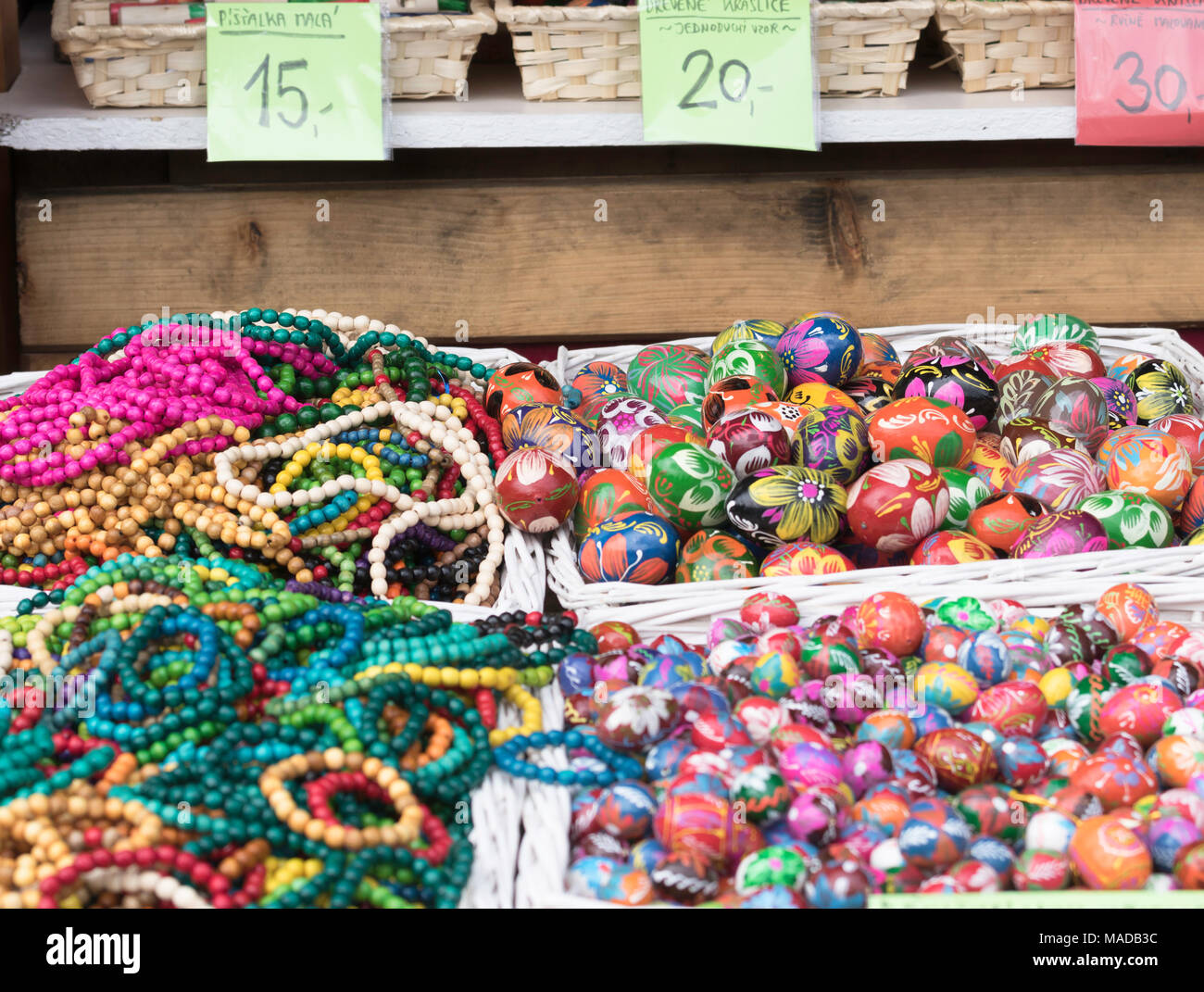 Decorated wooden Easter Eggs and beeds, lying in white straw basket at an outdoor stall. Stock Photo