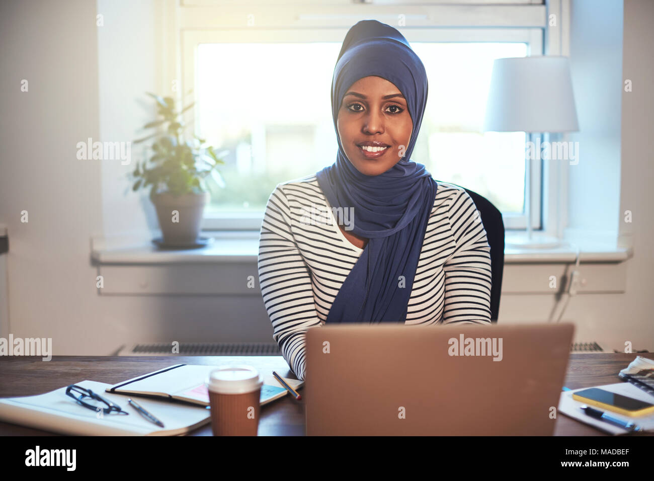 Smiling young Muslim female entrepreneur wearing a hijab sitting in her home office working online with a laptop Stock Photo