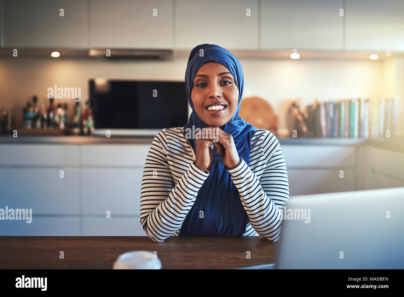 Confident young Arabic female entrepreneur wearing a hijab working on a laptop while sitting at a table in her kitchen Stock Photo