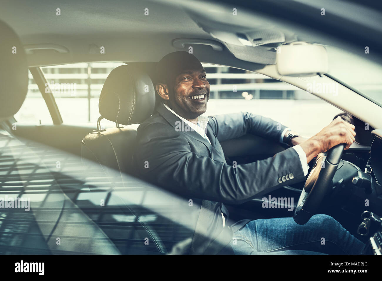 African businessman wearing a blazer and smiling while driving his car during his morning commute through the city - Stock Image