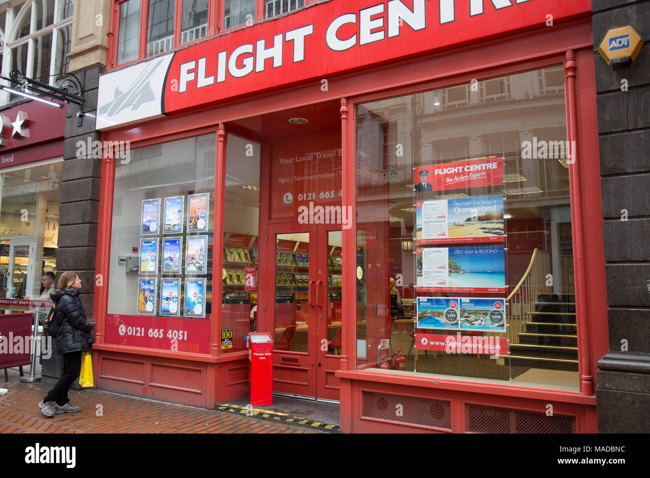 Young female looking at adverts in the window of the Flight Centre store in Birmingham, England. - Stock Image