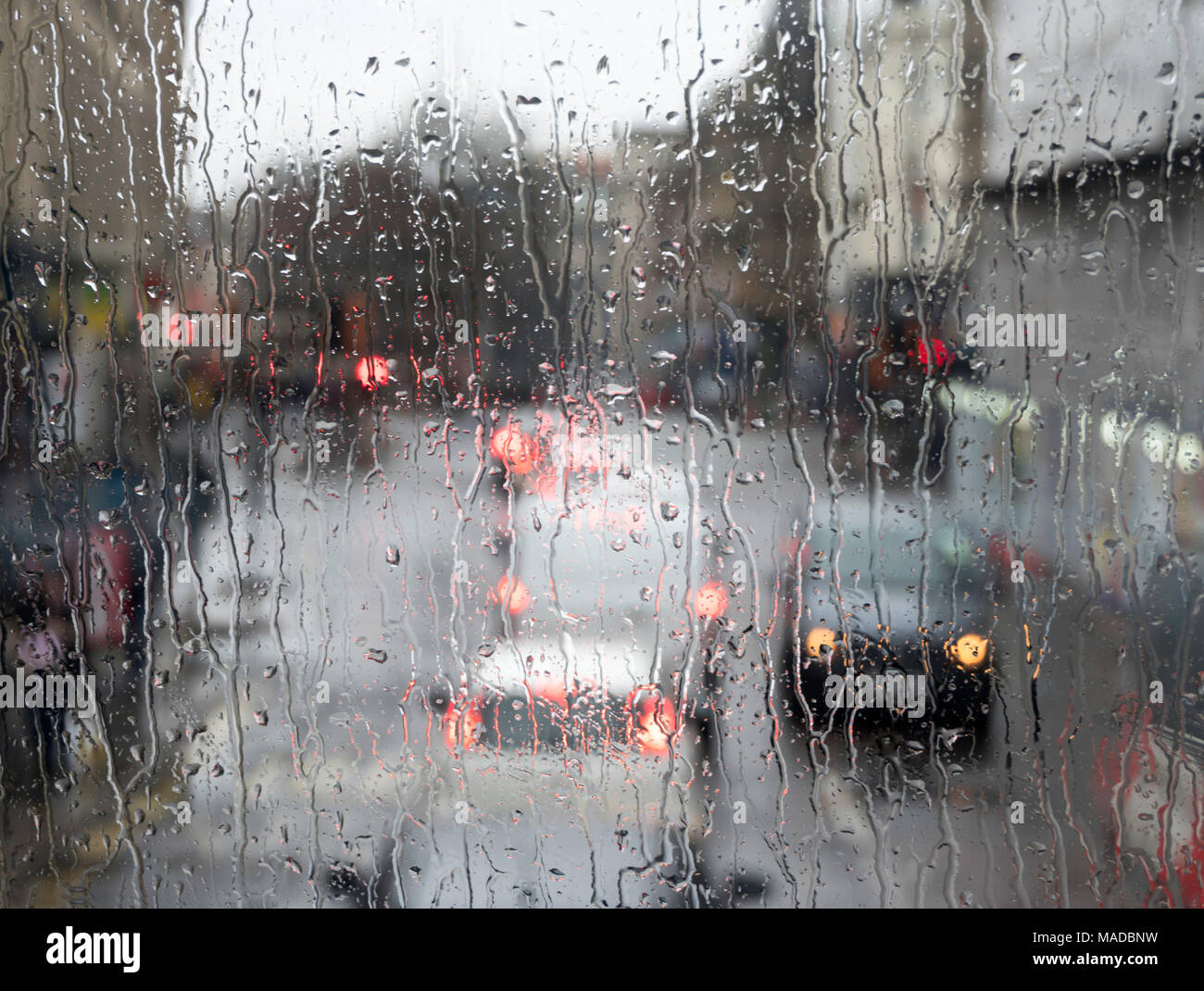 Road traffic seen through heavy rain on window, Newcastle city centre, north east England, UK - Stock Image