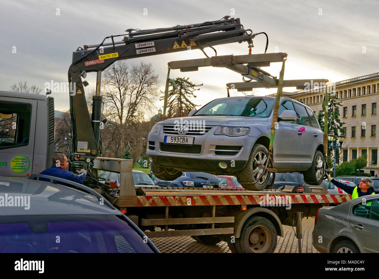 Illegally parked car being removed and impounded.( Registration number has been changed and randomised. EU plate) - Stock Image