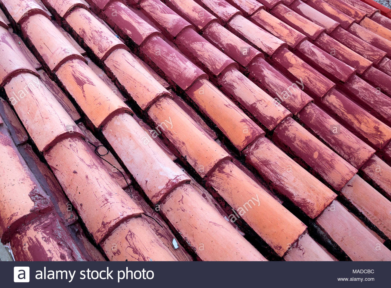 Taken on the diagonal, roughly cast terracotta tiles have been installed on a roof.  Maroon painting is evident on some. - Stock Image