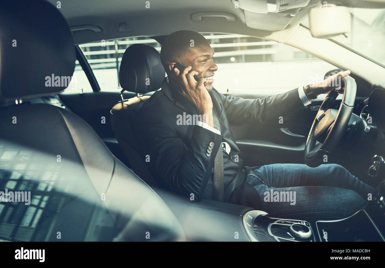 Smiling African businessman wearing a blazer talking on a cellphone while driving his car through the city during his morning commute to work - Stock Image