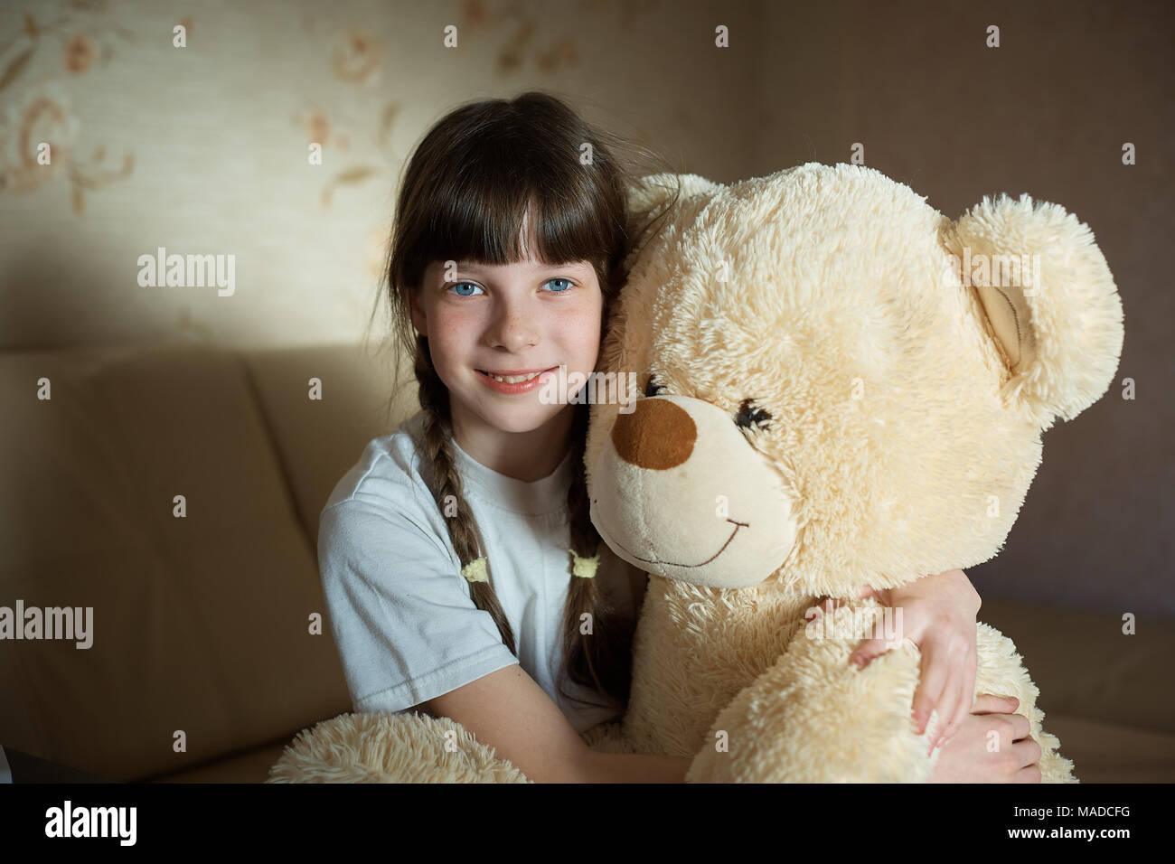 little girl hugging teddy bear indoor in her room, devotion concept, big bear toy - Stock Image