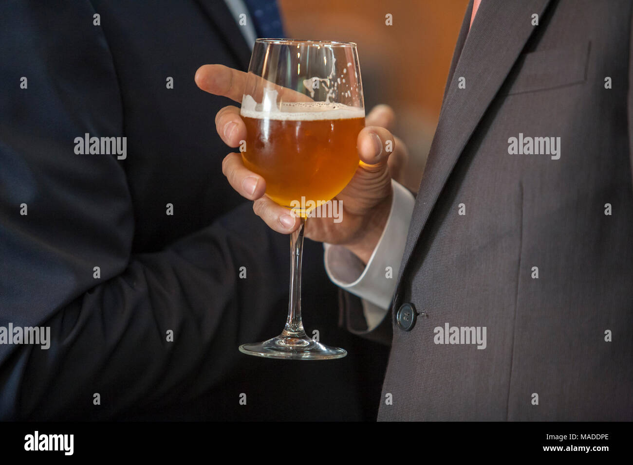 People drinking beer at Welcome cocktail party with formal wear. Two men with glass chalice. Selective focus - Stock Image