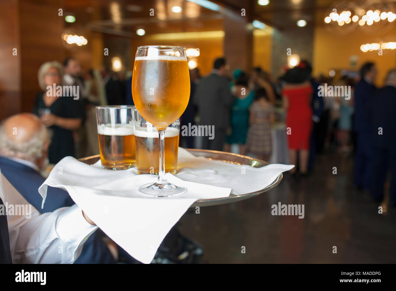People drinking beer at Welcome cocktail party with formal wear. Waiter holds a tray with glasses and glass chalice - Stock Image