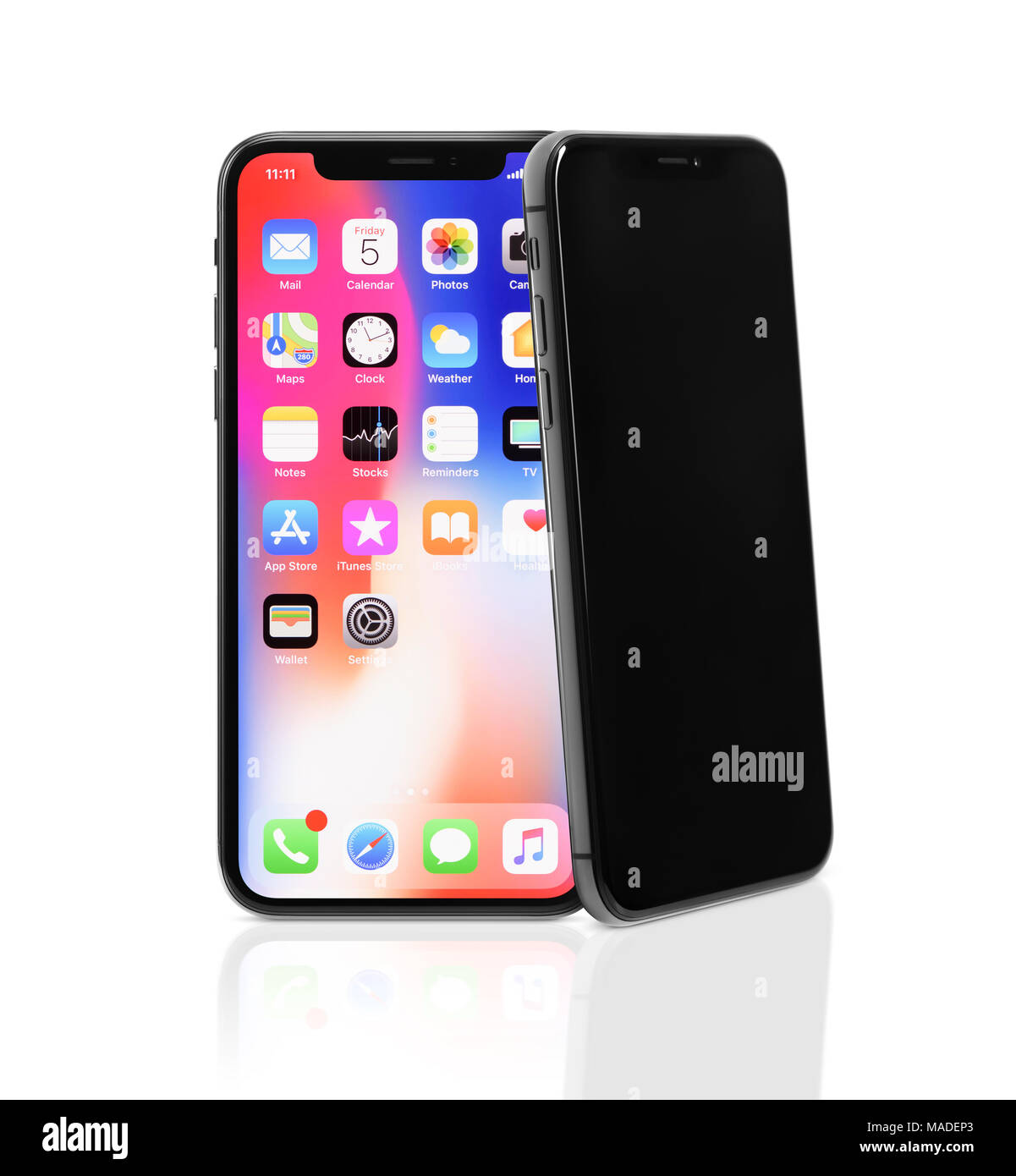 Two Apple iPhone X, large screen smartphones, product still life, one iPhone is leaning on another. The phones ares isolated on white studio backgroun Stock Photo