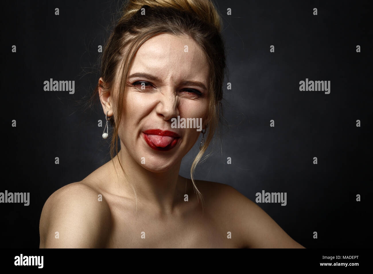fun woman grimacing show her tongue on black background - Stock Image