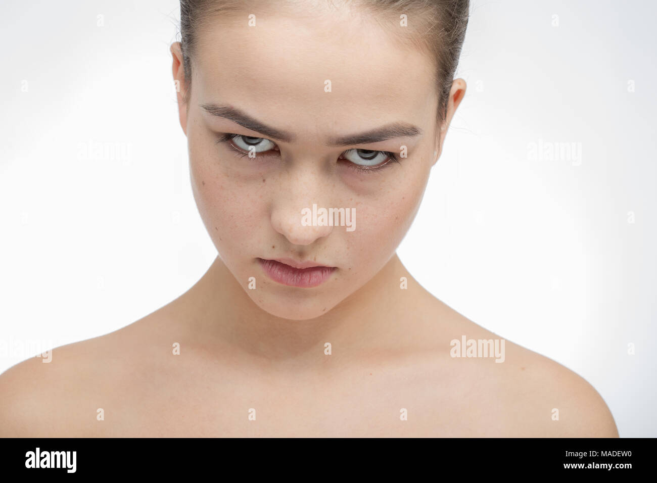 angry sullen girl on white background looking at camera - Stock Image