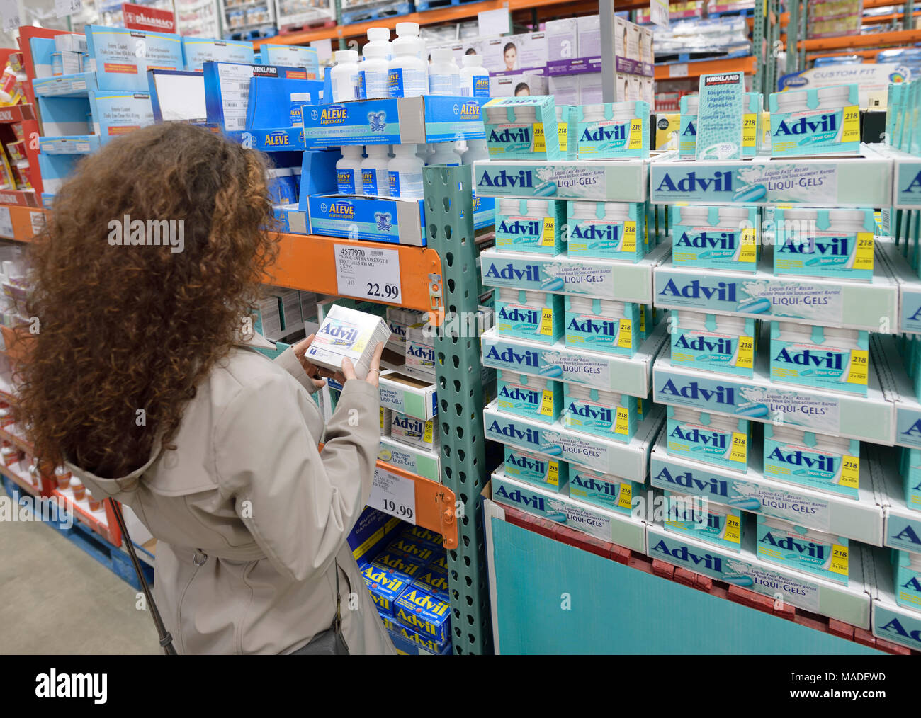 Woman picking a box of Advil liqui-gels pain relief medications at Costco Wholesale membership warehouse store pharmacy section. British Columbia, Can Stock Photo
