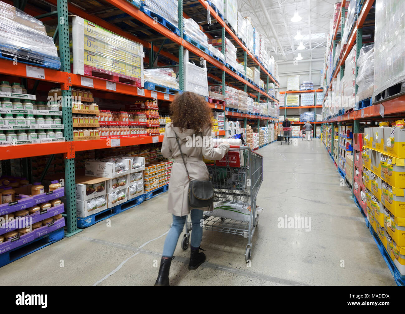 Woman with a shopping cart walking along the aisle of food and groceries section at Costco Wholesale membership warehouse store. British Columbia, Can Stock Photo
