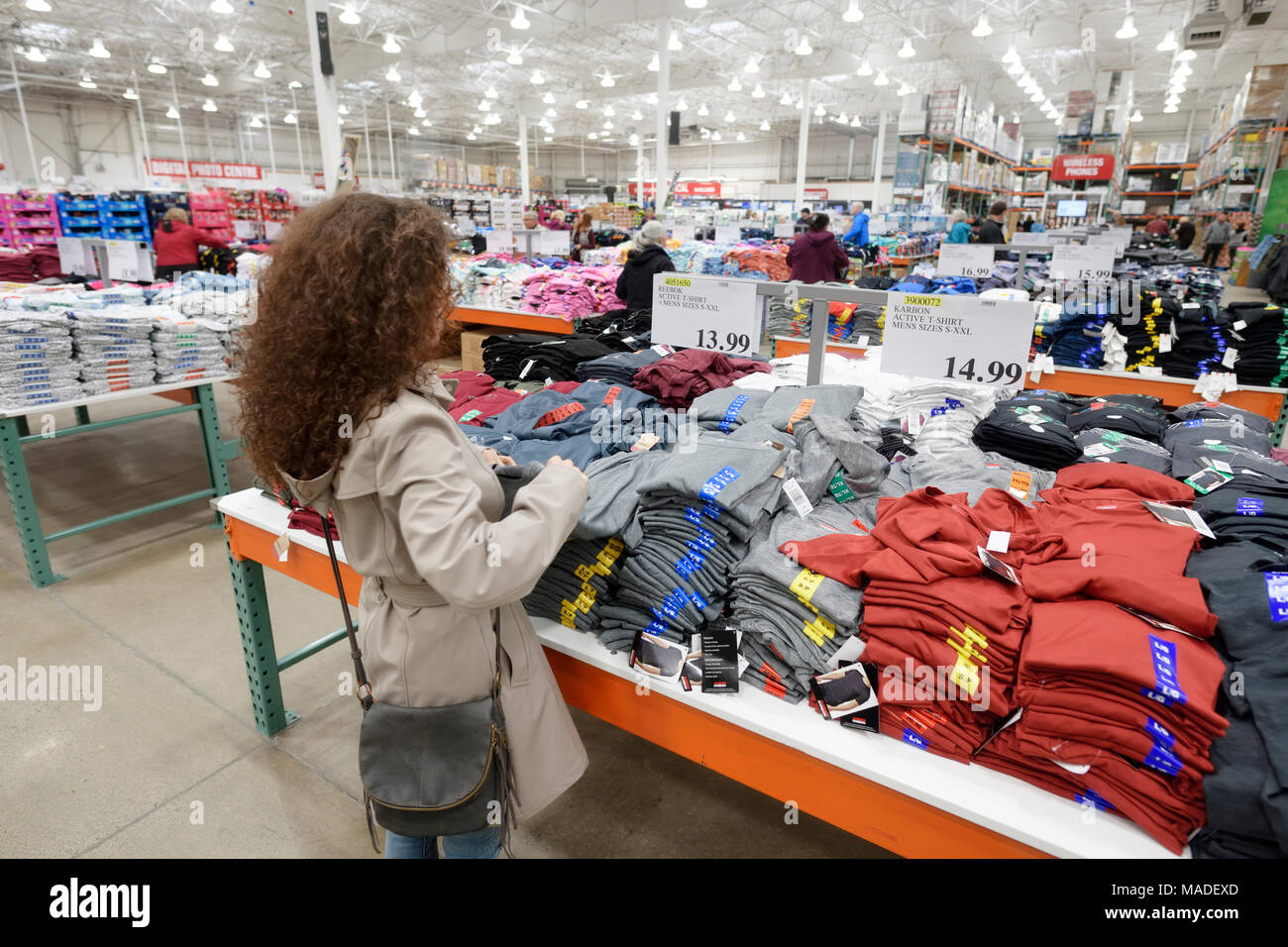 Woman picking a T-shirt at Costco Wholesale membership warehouse store men's clothing section. British Columbia, Canada 2017. - Stock Image