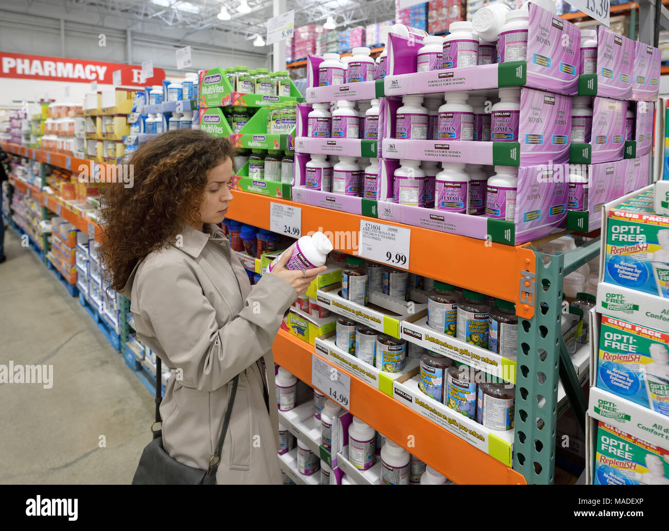 Woman reading indredients of Kirkland Women formula supplements at Costco Wholesale membership warehouse store pharmacy section. British Columbia, Can Stock Photo