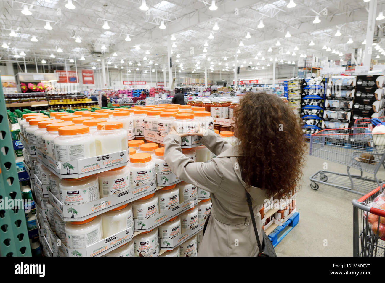 Woman picking a can of Kirkland coconut oil at Costco Wholesale membership warehouse store food section. British Columbia, Canada 2017. Stock Photo