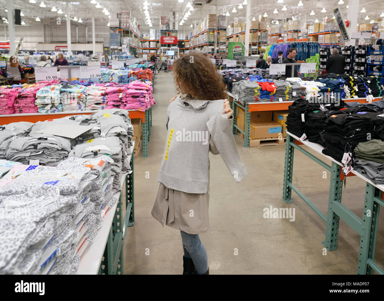 Woman trying on a sweater at Costco Wholesale membership warehouse store womens clothing section. British Columbia, Canada 2017. Stock Photo
