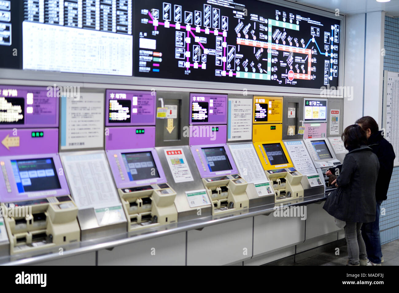 People buying train tickets from a subway station ticket machine, vending kiosk at a train station in Kyoto, Japan 2017 Stock Photo