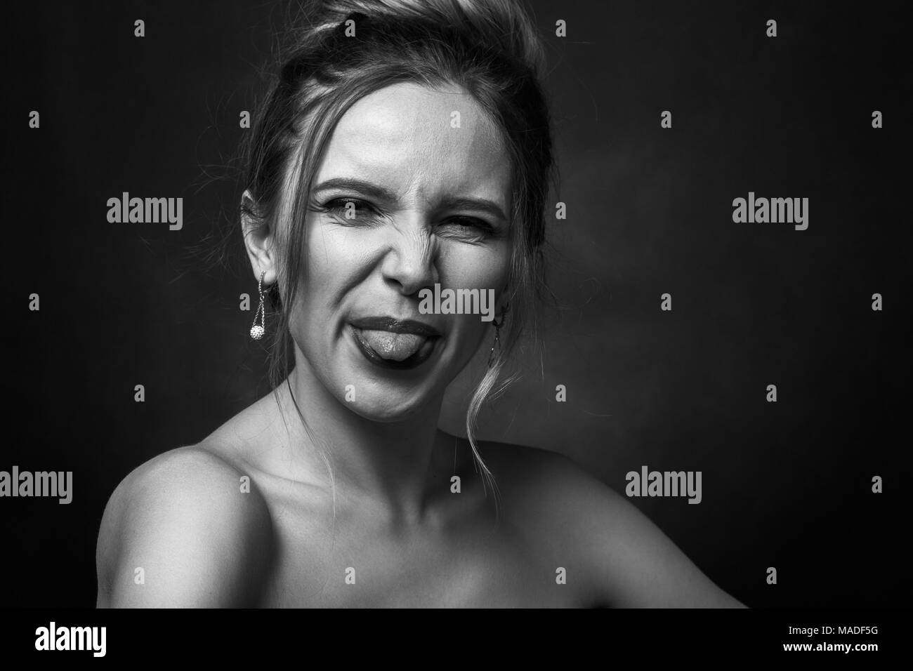 fun woman grimacing show her tongue on black background, monochrome - Stock Image