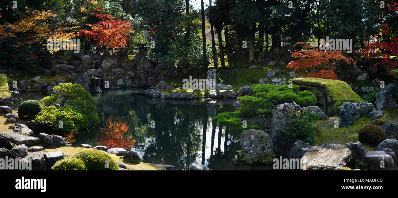 Panoramic scenery of a traditional Japanese Zen rock garden with a pond and a bridge leading to Fujito Ishi stones in the center, beautiful tranquil a Stock Photo