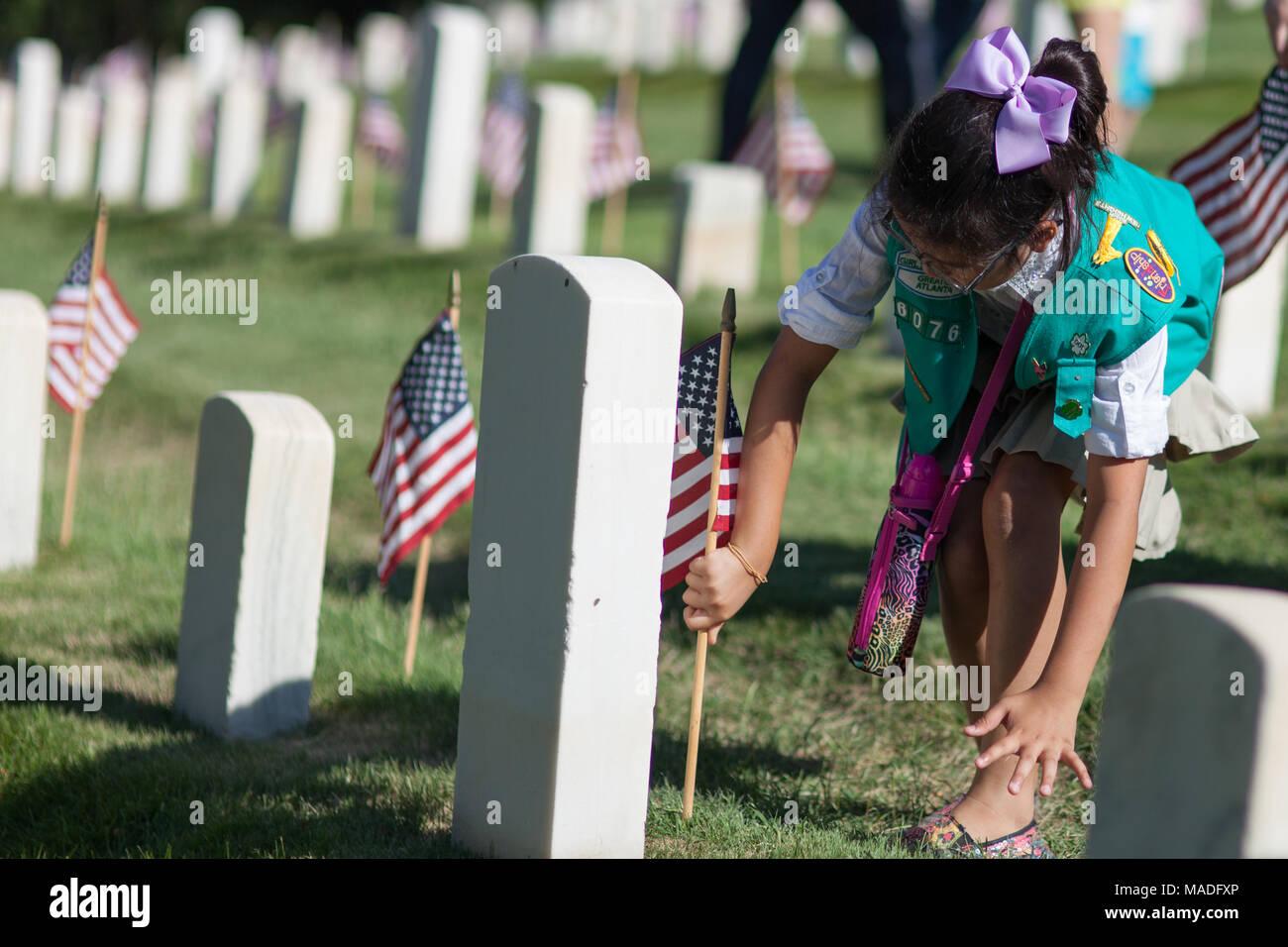 Girl Scout planting flag at civil war memorial cemetery Memorial Day weekend. - Stock Image