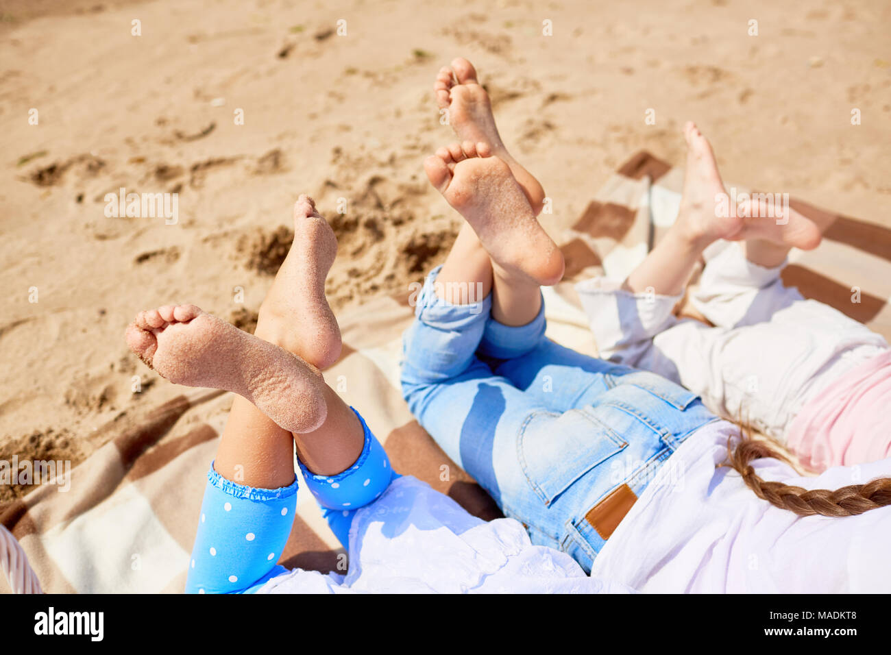 soles of bare feet of girls lying on sandy beach on hot summer day