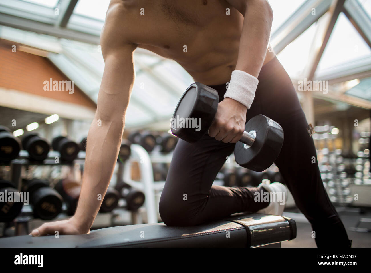 Shirtless guy with heavy dumbbell training his arm muscles while