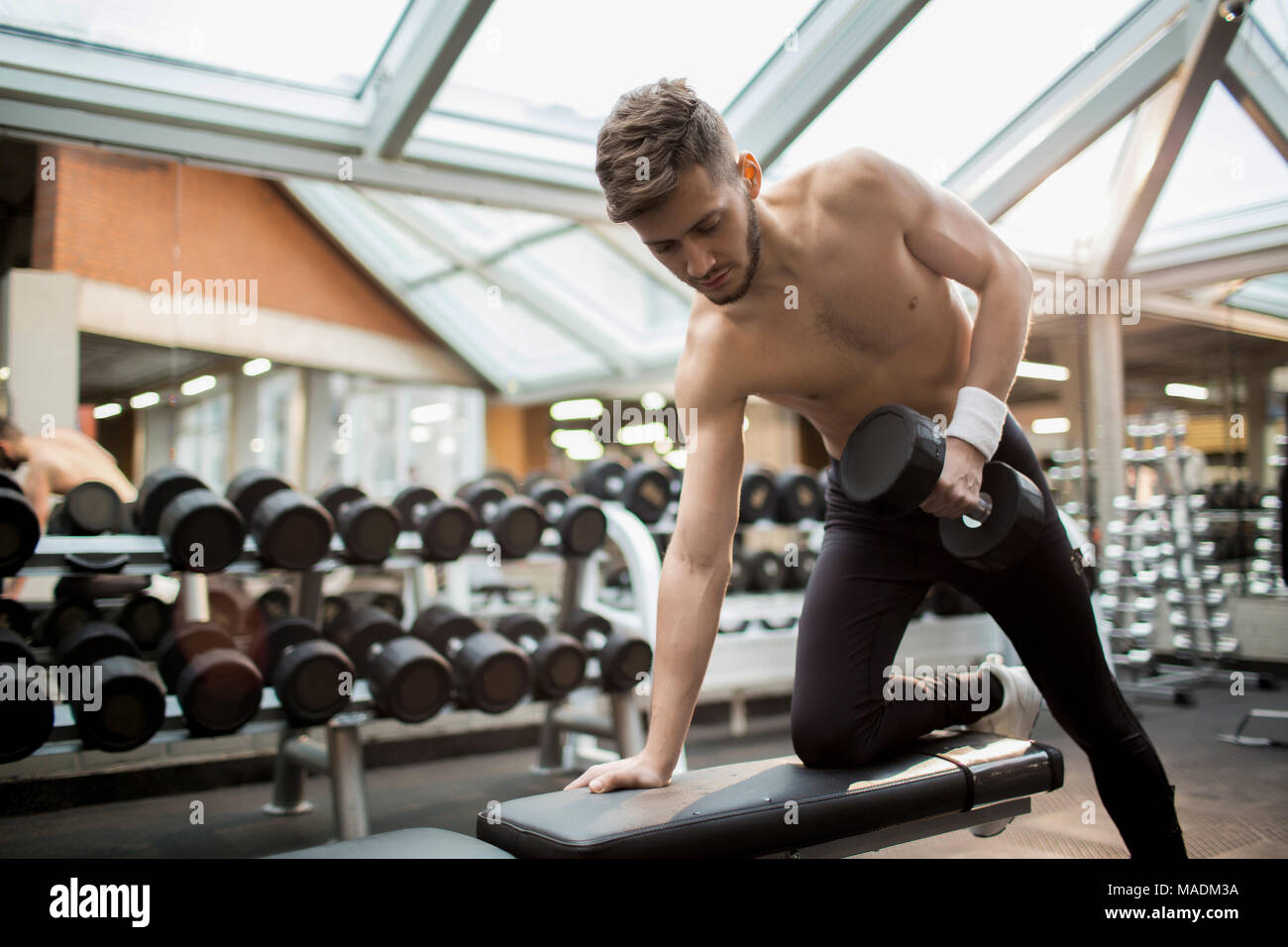 Young shirtless man in black leggins and sports-shoes leaning on right arm and bent knee while exercising with heavy dumbbell in gym - Stock Image